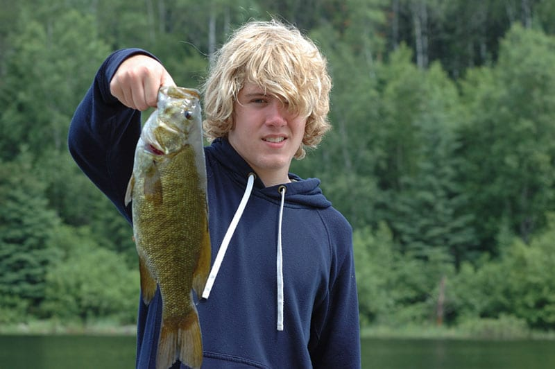 Young man holding a smallmouth bass.